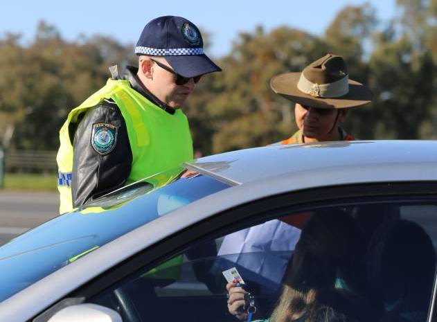 Soldiers and police check cars on their way through the border cross at Albury. Pictures: NSW Police