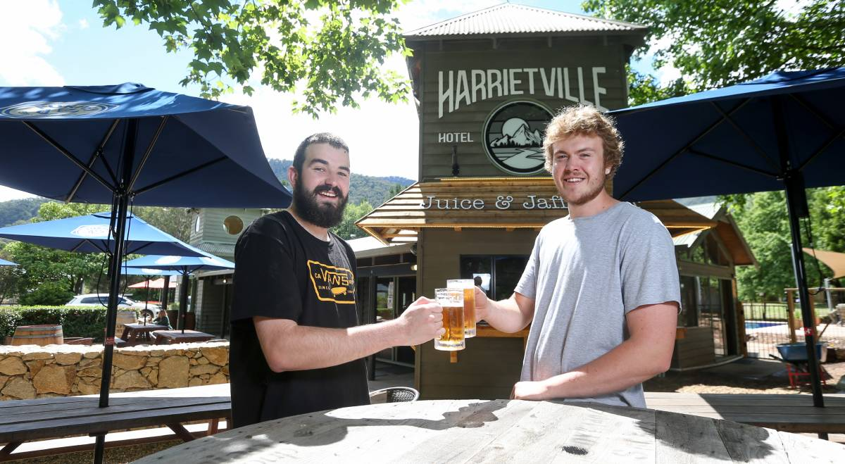 CHEERS: Harrietville Hotel-Motel staff Caleb Lawes and Josh Raymond said it has been great to see the pub thriving a year on from a tough bushfire season. Picture: TARA TREWHELLA