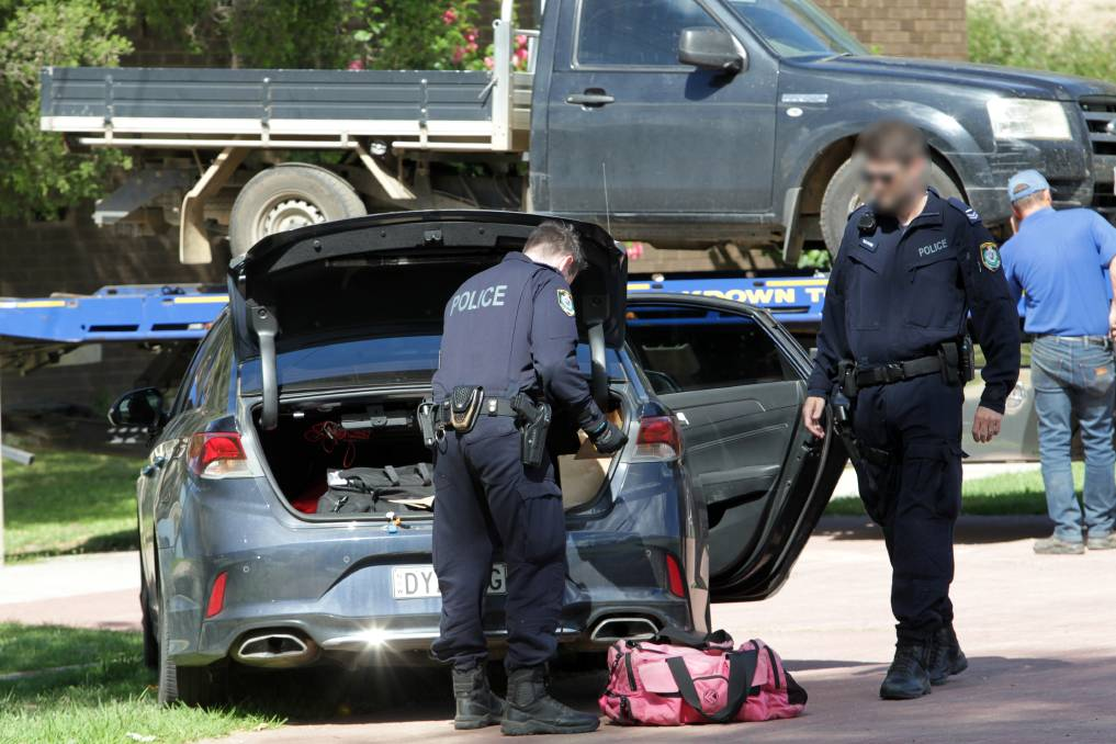 SEIZED: Police load bags of evidence into a car as part of an investigation into car thefts in the Albury region, including a dark Ford Ranger. The Ford was towed from Burrows Road on Friday after being recovered.
